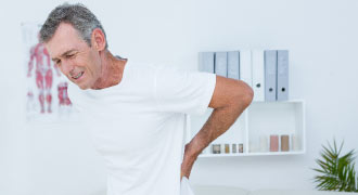 older male in a white t-shirt with hand on back pain and suffering from back pain