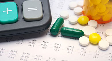 medical expenses with calculator and green white and yellow medicine pills laying on top